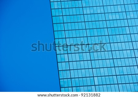 Looking up at a Modern Skyscraper building against the blue sky - stock photo
