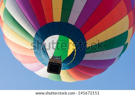 Looking up at a rainbow colored hot air balloon. - stock photo