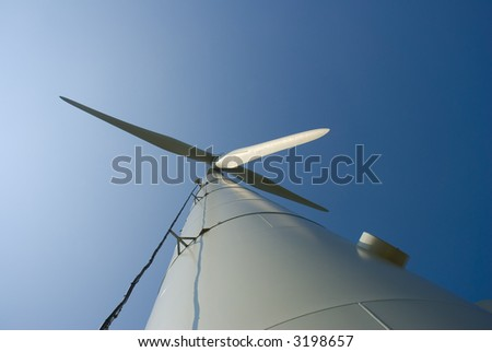Looking up at a three-bladed wind turbine. Low angle shot. - stock photo