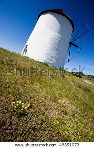 Looking up at a windmill from a diagonal view, with clear blue skies in the background and a foreground of lush greenery - stock photo