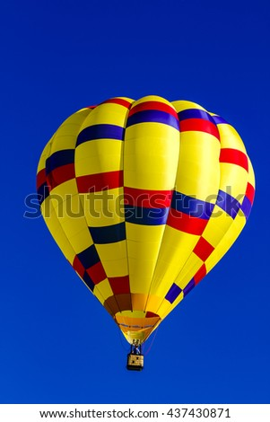 Looking up at bright yellow, blue and red hot air balloon floating in early morning blue sky