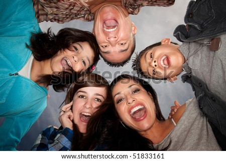 Looking up at Hispanic family in huddle - stock photo