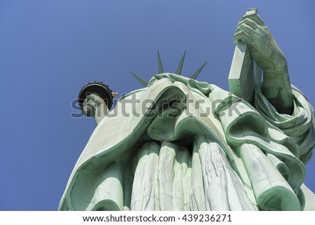 Looking up at Lady Liberty holding torch and tablet - stock photo