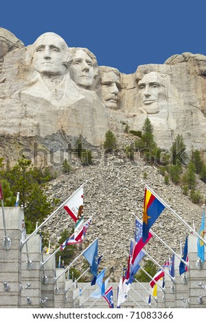 Looking up at Mount Rushmore with state flags at the base - stock photo