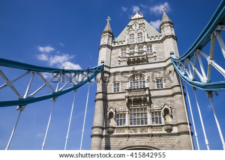 Looking up at one of the towers of Tower Bridge which spans over the River Thames in London. - stock photo