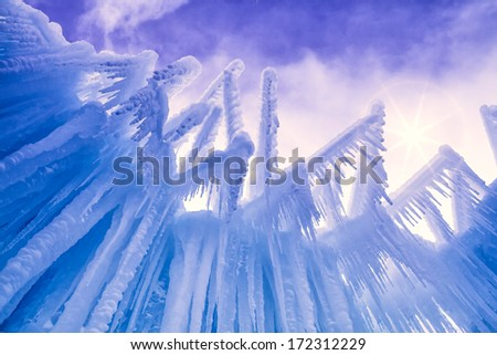 Looking up at sky at abstract ice and icicle formations on cold winter day after freshly fallen snow - stock photo