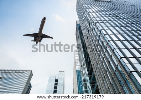 looking up at the airplane and modern glass office building