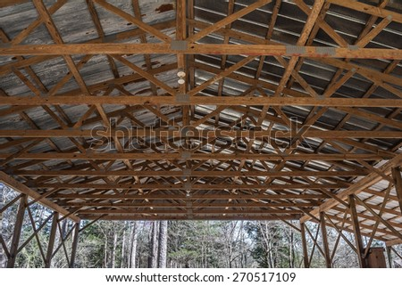 Looking up at the ceiling joists and rafters of an open wall building. - stock photo