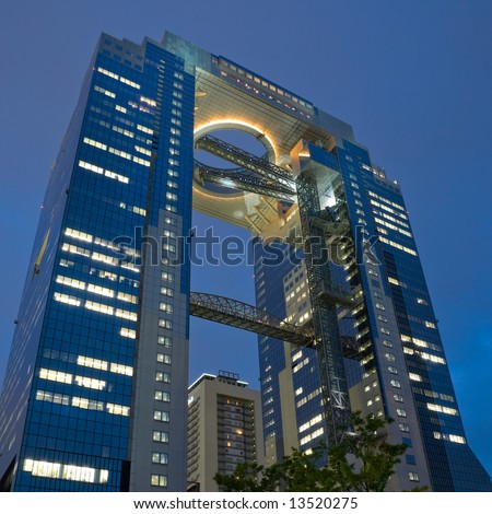 Looking up at the illuminated view of the top of a tall office building in Osaka, Japan at dusk