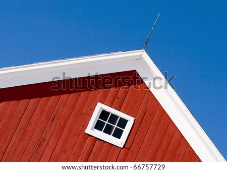 Looking up at the top of a gabled roof on a red barn. - stock photo