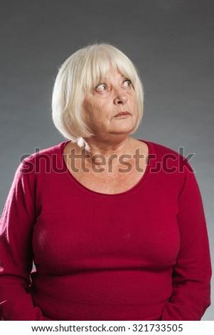 Looking up - female senior portrait series on grey background. - stock photo