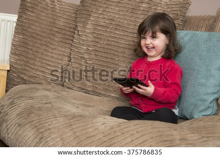 Looking up from tablet and laughing - stock photo