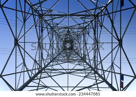 Looking up metal electricity pylon - stock photo