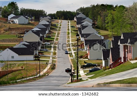 Looking up the street of a neighborhood of midsize homes. - stock photo