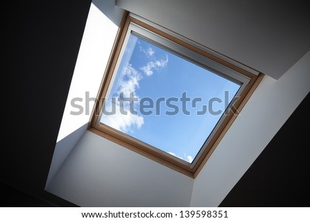 Looking up to the blue cloudy sky through modern square ceiling window - stock photo