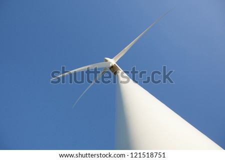 looking up to wind turbine and blue sky - stock photo