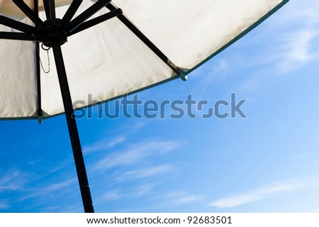 Looking up under a tilted white beach or market umbrella against blue sky on a sunny day. White canvas with black wooden frame.  Copy space for text