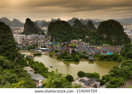 Lookout over Guilin City in SouthProvince, South China. Peacful Atmosphere in the morning. Sunrise behind the mountains. Boat in the lake. Ancient Pagoda in the middle, center of the picture. - stock photo