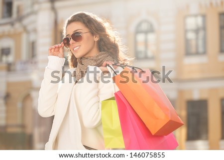 Looks great with her new sunglasses. Beautiful young women in sunglasses holding the shopping bags and looking away - stock photo