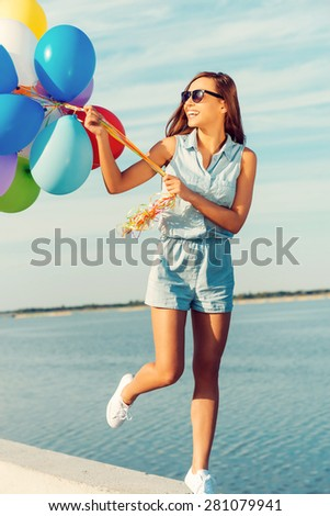 Looks like a party for one. Joyful young woman holding colorful balloons and smiling while walking outdoors  - stock photo