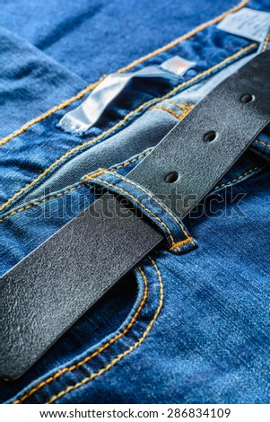 Loop of jeans with black leather belt - stock photo