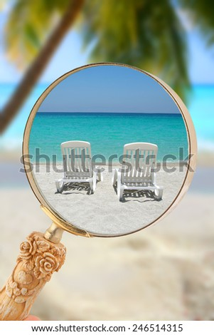 Loop or magnifying glass enlarging the view of two loungers on a tropical beach in the Caribbean - stock photo