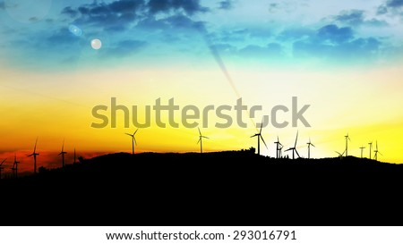 LOOP windmill turbines harnessing clean, green, wind energy silhouetted in the sunrise/sunset sky with sun rays. Green energy - stock photo