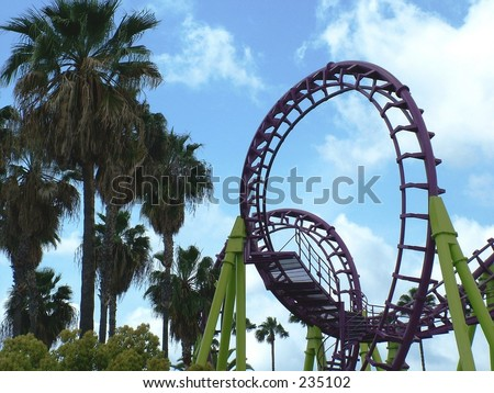 Looping roller coaster, back lit - stock photo