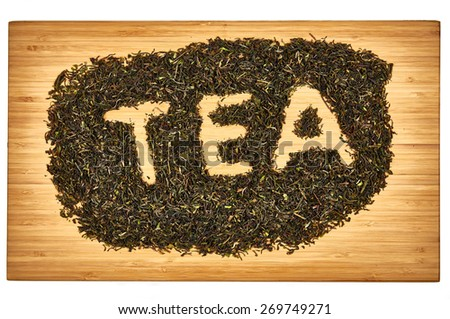 Loose Darjeeling tea spelling tea on wooden cutting board - stock photo