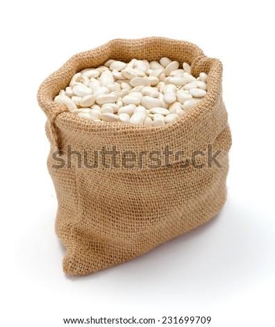 Loose dry haricot beans in burlap sack - stock photo