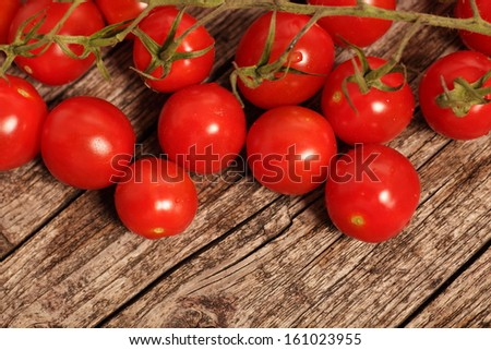 Loose fresh uncooked ripe red cherry tomatoes together with a bunch still o the vine arranged on a rustic wooden surface with copyspace