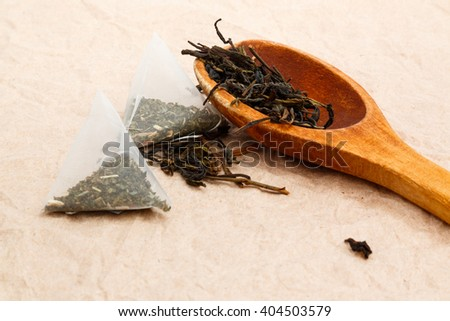loose green tea, tea bags and a spoon on a wooden background  - stock photo