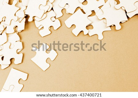 Loose jigsaw puzzle pieces on brown background