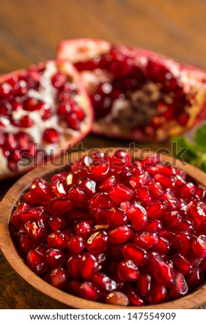 Loose pomegranate (Punica granatum) seeds in a wood bowl shot on a wood table. There are pieces of ripe pomegranate fruit & green mint leaves in the background.  Pomegranates are a super food.
