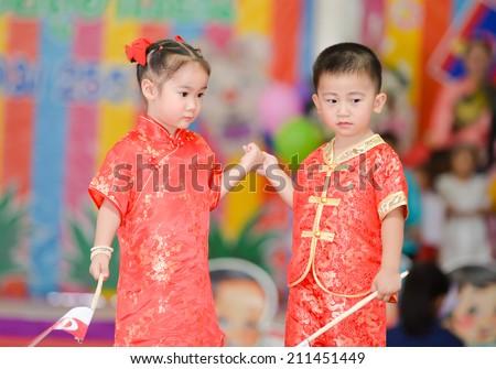 LOPBURI -AUG 15 : Unidentified cute boy and girl wearing national Singapore dress walk the runway at Banjongrat school on August 15, 2014 in Lop buri, Thailand - stock photo