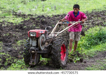 LOPBURI, THAILAND - JULY 10, 2016 : Tiller with tractor on rice field before seeding. Farmers plowed soil in the rainy season. - stock photo