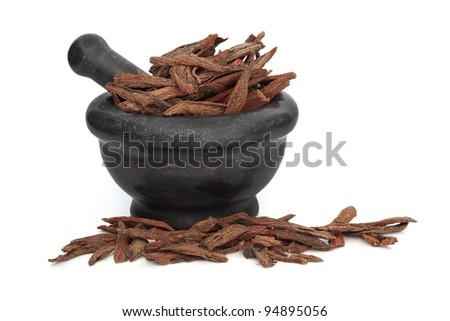 Lophatherum stem used in traditional chinese herbal medicine in a black granite mortar with pestle isolated over white background. Dan shen. Radix codonopsitis pilosulae. - stock photo