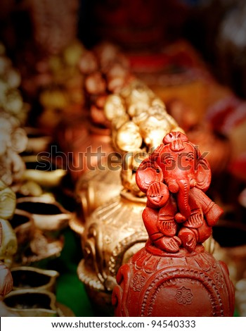 Lord Ganesh idol made of clay and painted red followed by golden colored Ganesha statues. - stock photo