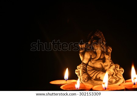 lord ganesha with beautiful diya at diwali - stock photo