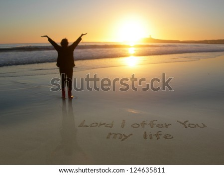 Lord I Offer You My Life handwritten in the sand with a woman's outstretched arms
