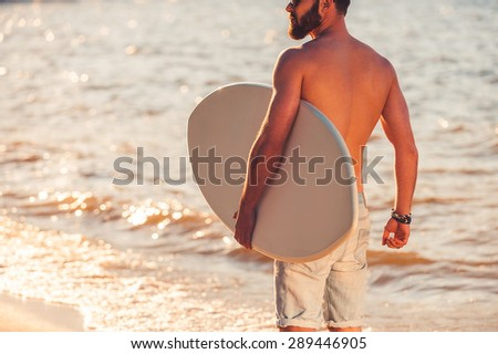 Lord of wave. Cropped image of shirtless young man holding skimboard and looking away while walking along the beach