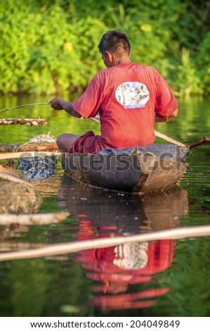 LORETO, PERU - JANUARY 02: Unidentified locals fishing in the river in the middle of the Amazon Rain Forest, on January 02, 2010 in Loreto, Peru.  - stock photo