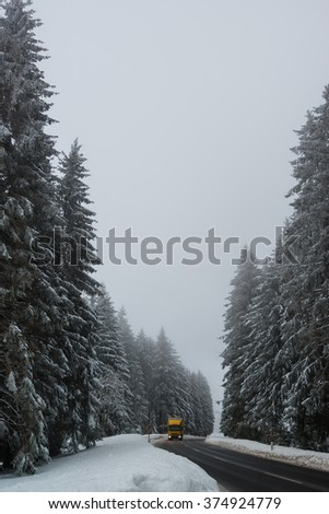 Lorry driving on a road in snowy winter landscape with red boundary posts - stock photo