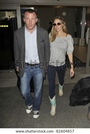 LOS ANGELES-APRIL 15: Actor/producer Guy Richie ex husband of singer Madonna with girlfriend at LAX airport. April 15 in Los Angeles, California 2010 - stock photo