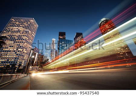 Los Angeles at night. Long exposure shot of blurred bus speeding through night street. - stock photo