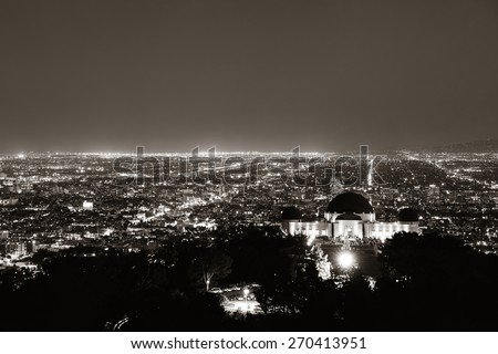 Los Angeles at night with urban buildings and Griffith Observatory - stock photo