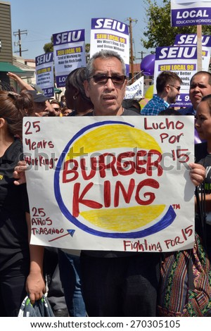 LOS ANGELES, CA   APRIL 15, 2015: A protestor holds a hand-made a sign with a Burger King logo advocating raising the minimum wage during a demonstration in Los Angeles on April 15, 2015.