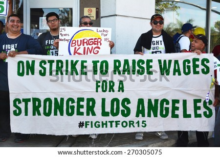LOS ANGELES, CA   APRIL 15, 2015: Protesting fast food workers hold a banner advocating raising the minimum wage for fast food workers during a demonstration in Los Angeles on April 15, 2015. - stock photo