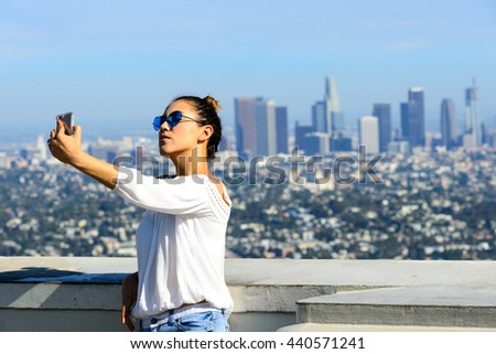 LOS ANGELES, CA - JUNE 19, 2016: Unidentified young woman taking selfies against the downtown of Los Angeles from Griffith Observatory, Los Angeles, California