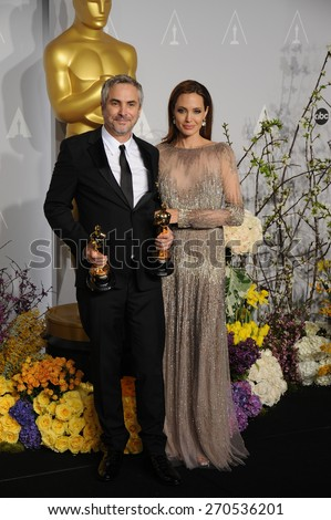 LOS ANGELES, CA - MARCH 2, 2014: Alfonso Cuaron & Angelina Jolie at the 86th Annual Academy Awards at the Dolby Theatre, Hollywood.